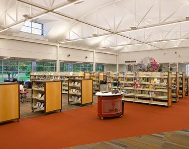 A picture of the Cozby Library and Community Commons. Image includes a help desk and book shelves.