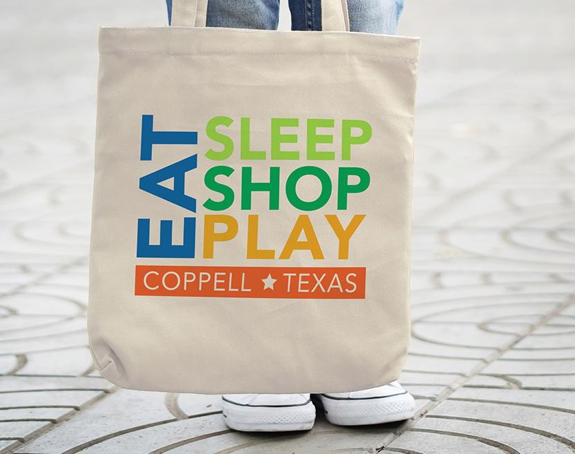 "Person holding tote bag that says ""Eat, Shop, Play, Coppell, Texas"""